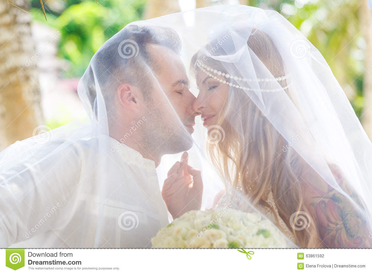 Beautiful young bride in the veil, with wedding bouquet of white