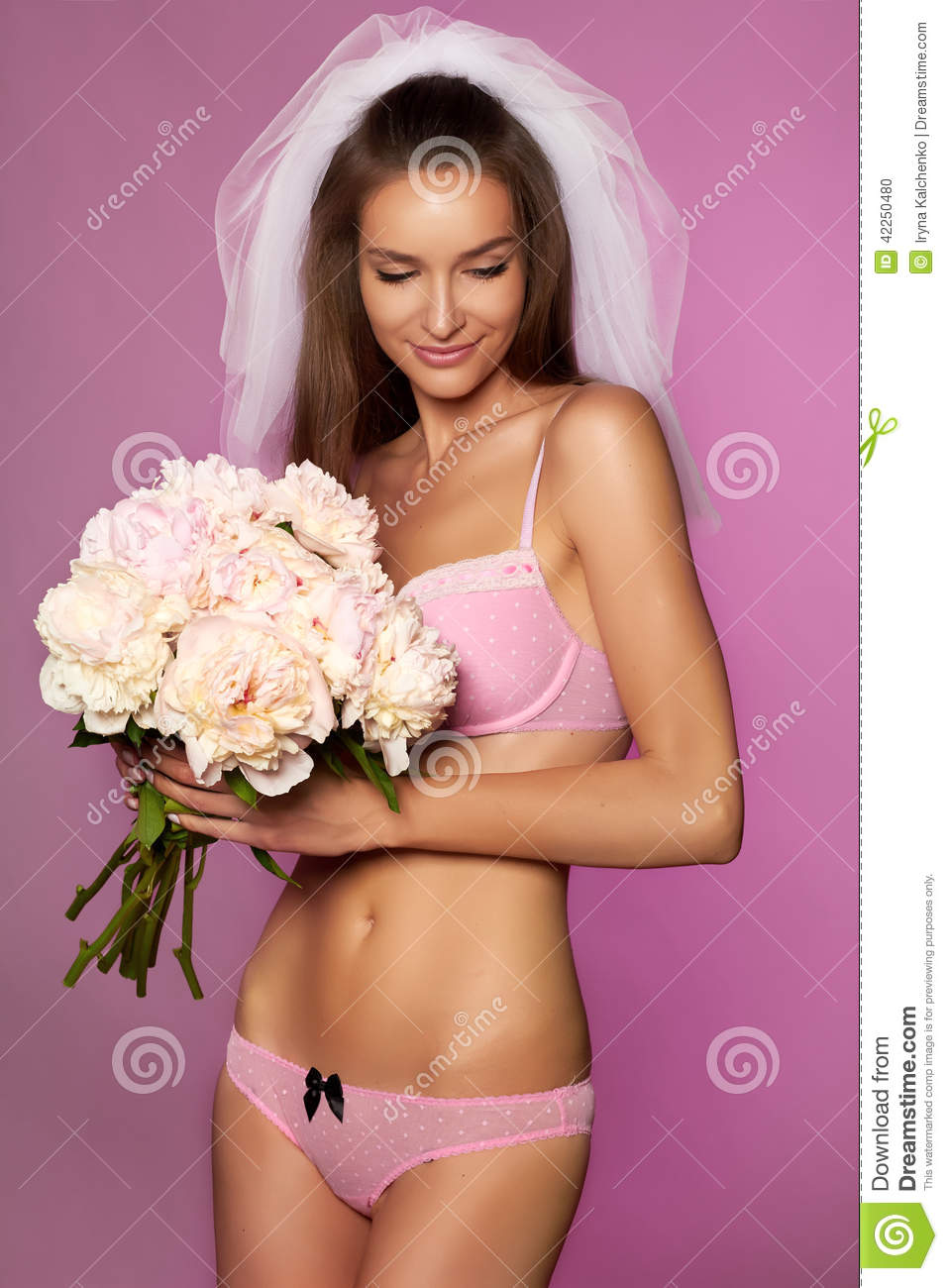 569ab7ed8b8 Beautiful young bride in white veil and pale pink lace lingerie with bouquet  of peonies in