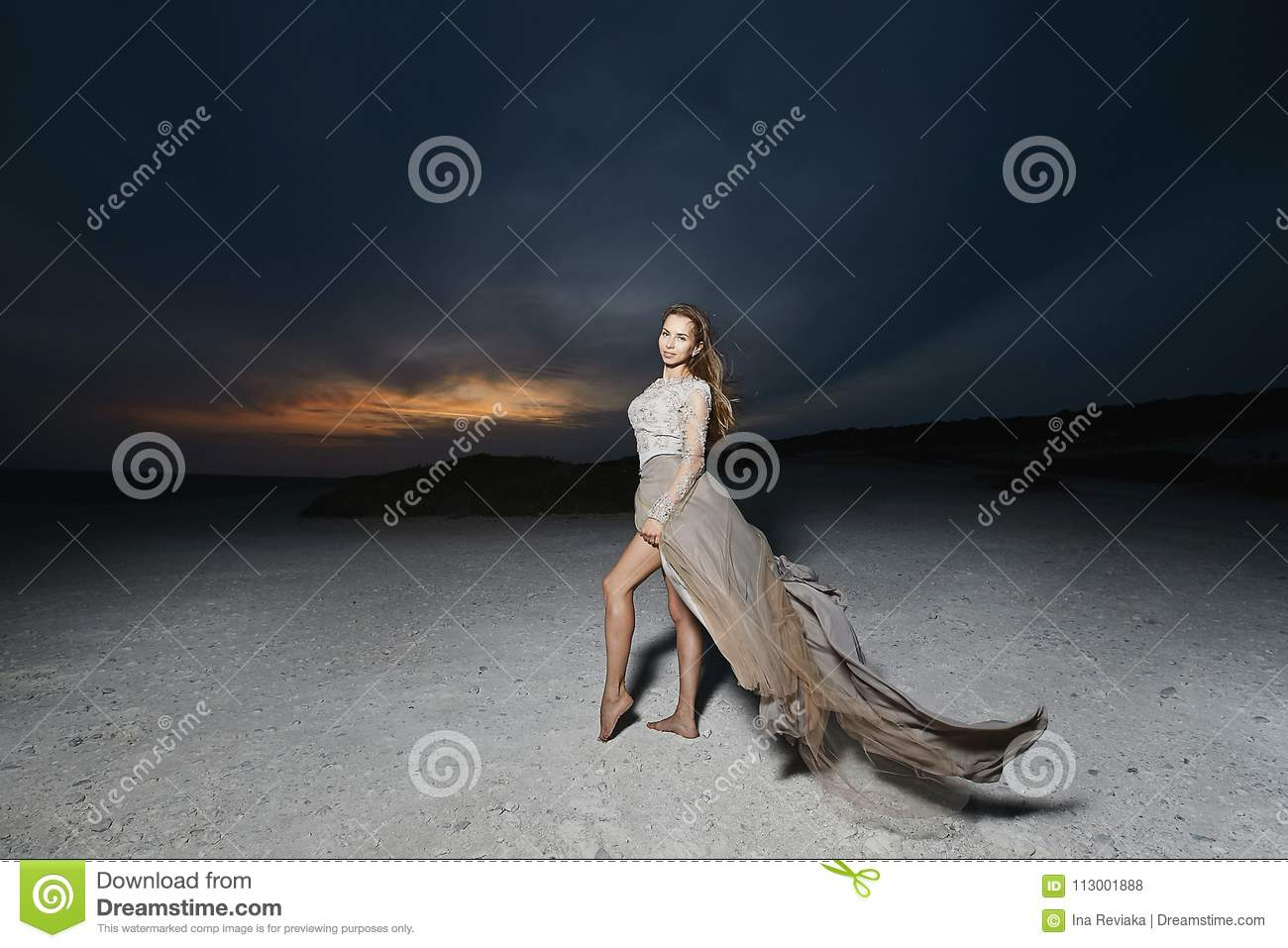 Beautiful and young brunette model woman, in beige lace dress, posing at the sunset