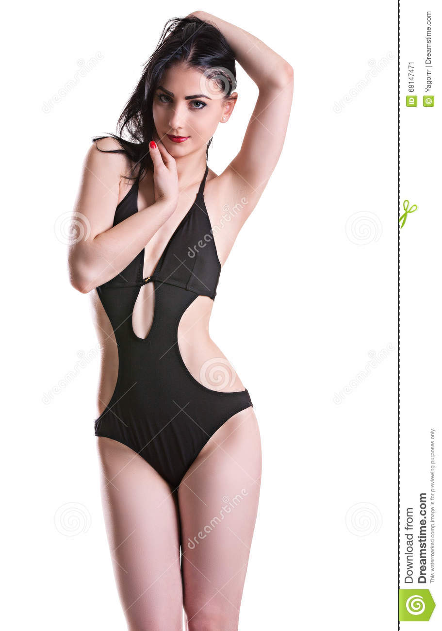 c01cbb7d7a0 Young beautiful brunette in a black bathing suit is closed, isolated on white  background