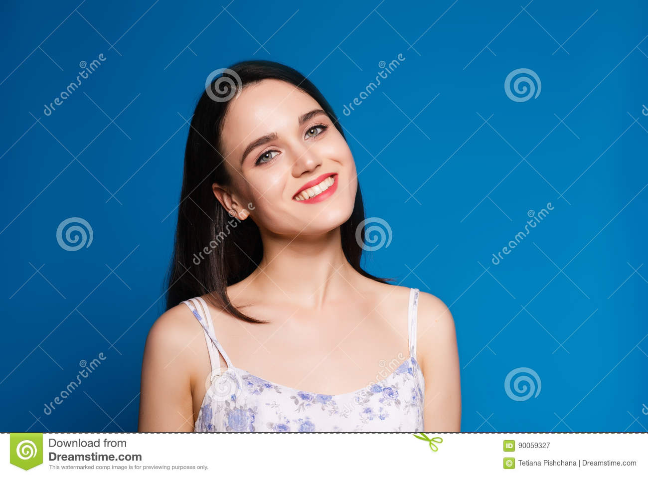 Beautiful young brunette woman on a blue background in the studio