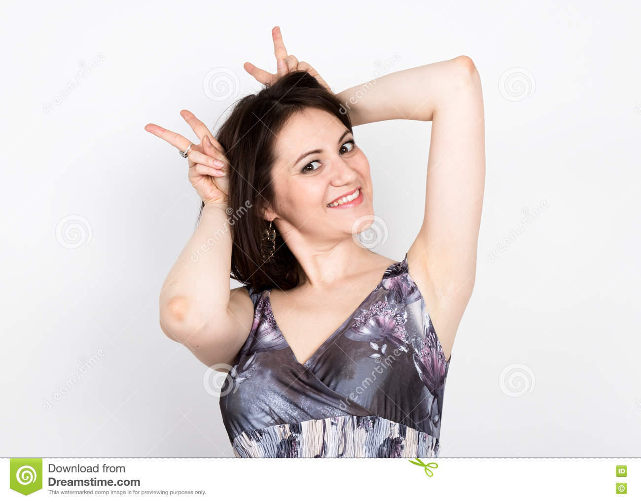 Beautiful young brunette woman in a colorful dress posing and expresses different emotions. woman s hands shows various