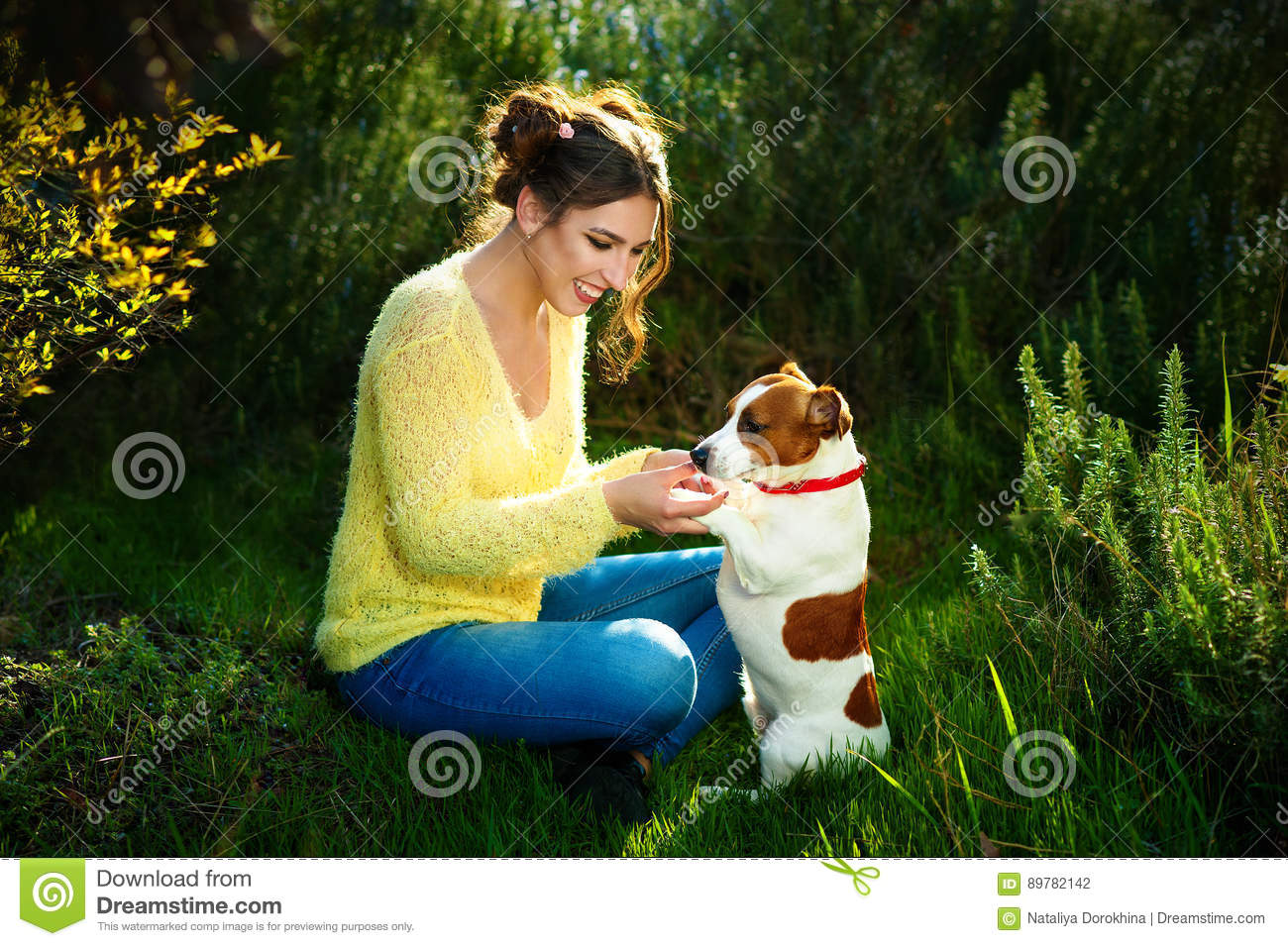 Beautiful young brunette woman enjoying in park outdoors together with her gorgeous Jack Russell terrier - sitting on