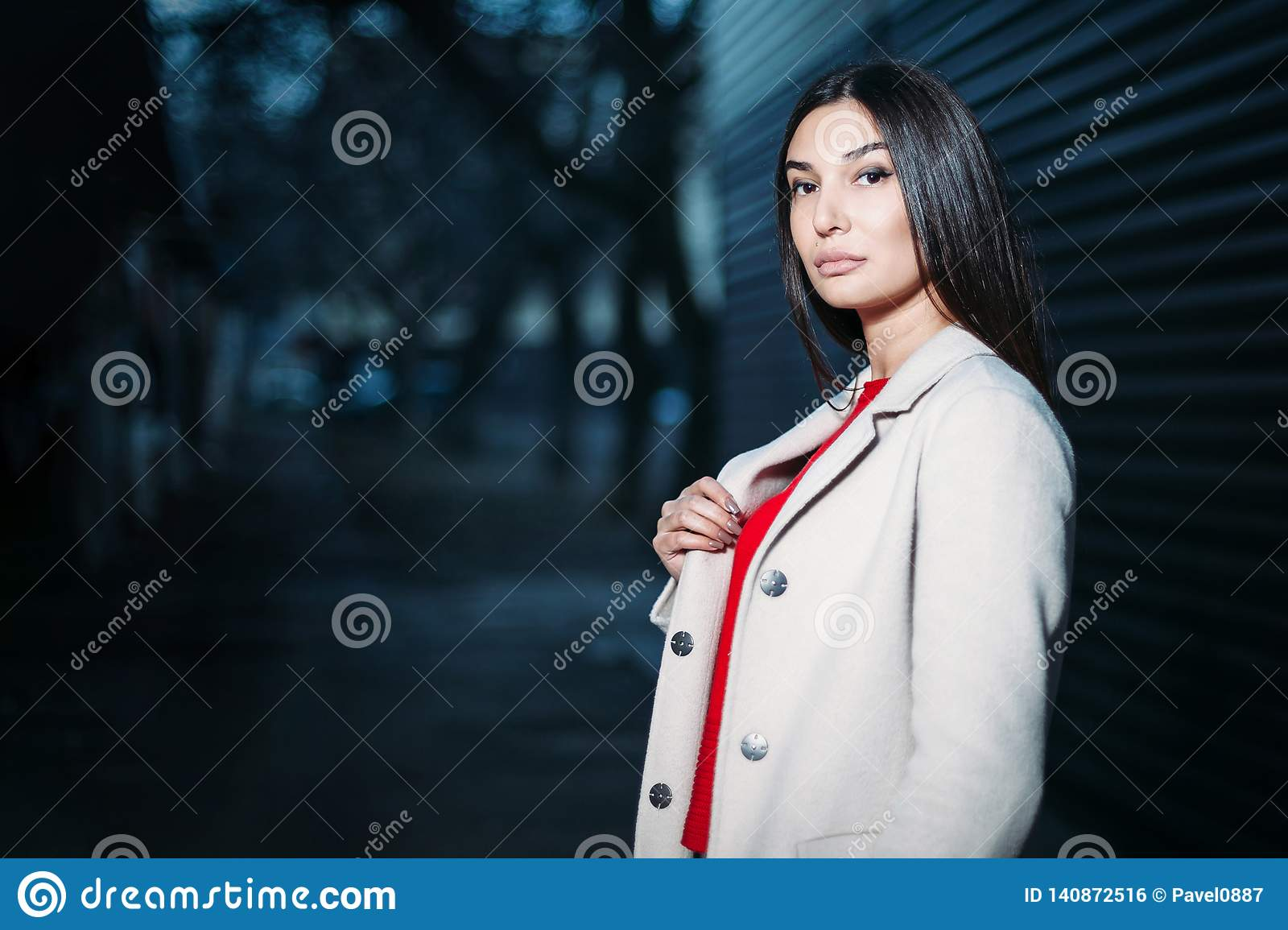 Beautiful young brunette woman in red blouse white coat evening outdoors. copy space
