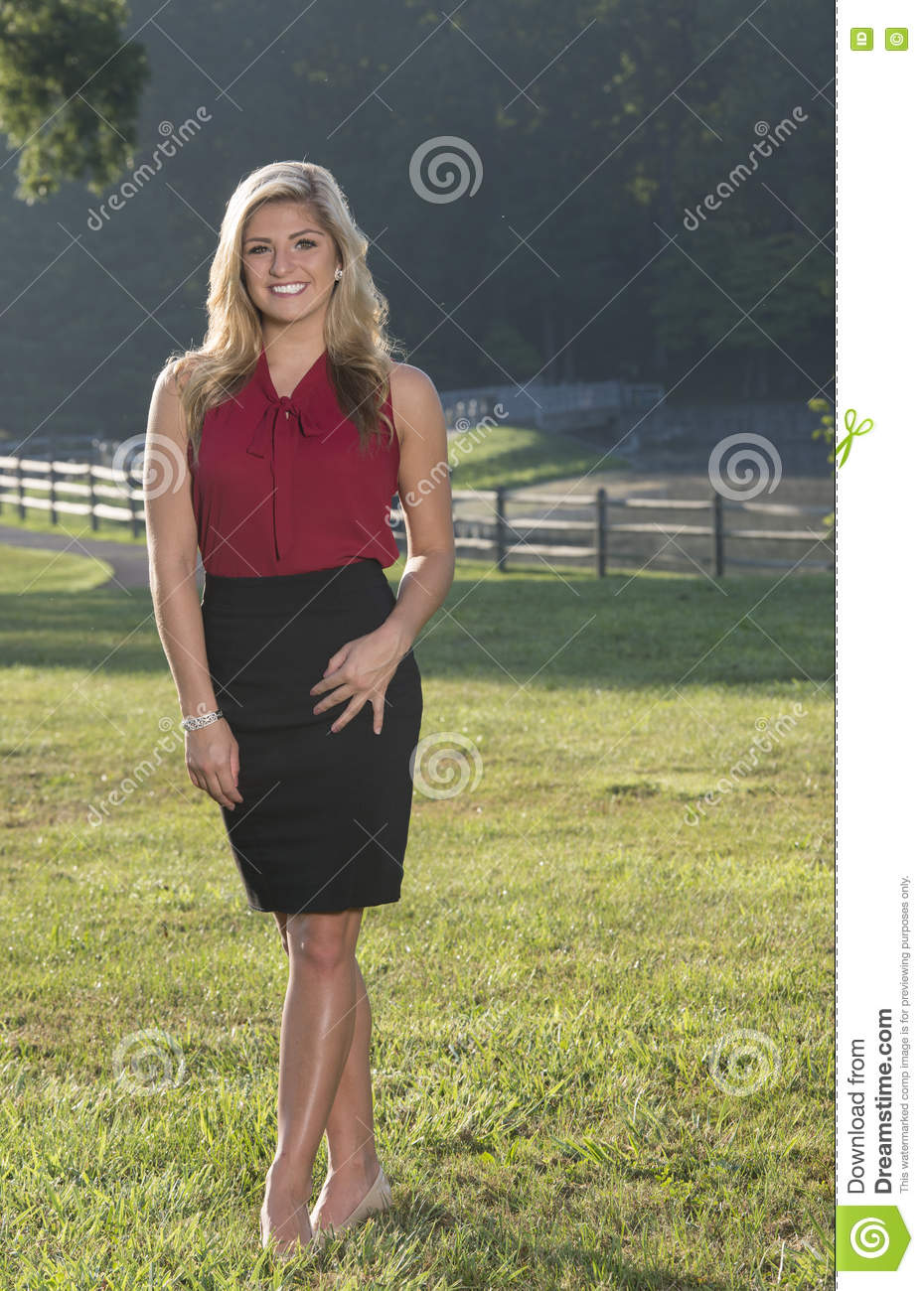 0d0e72c76df1cd Beautiful young Caucasian woman in business attire (red blouse and black  skirt) stands at sunrise in a country scene - headshot
