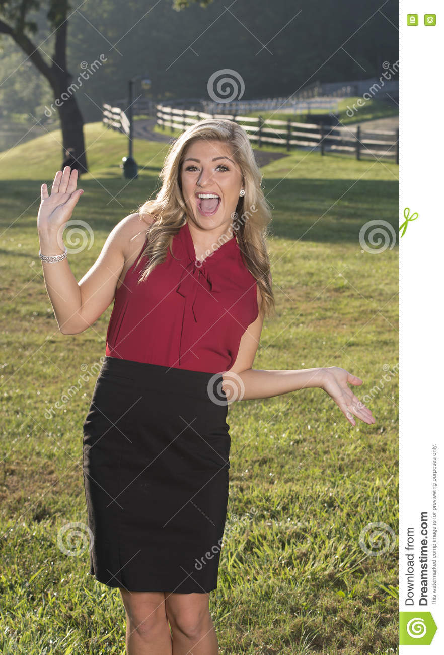e19edfc0ff21c2 Beautiful young Caucasian woman in business attire (red blouse and black  skirt) stands at sunrise in a country scene - fun expression