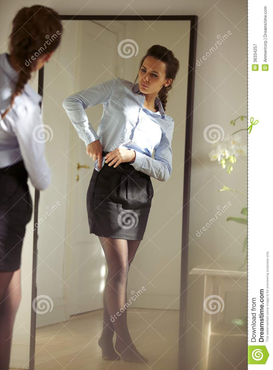 beautiful young businesswoman getting dressed stock image