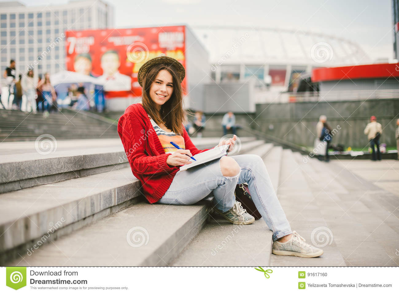 A beautiful, young Caucasian girl sitting on the street smile, the joy, sit with notebook and pen in Ruhi. In the red sweater, jea