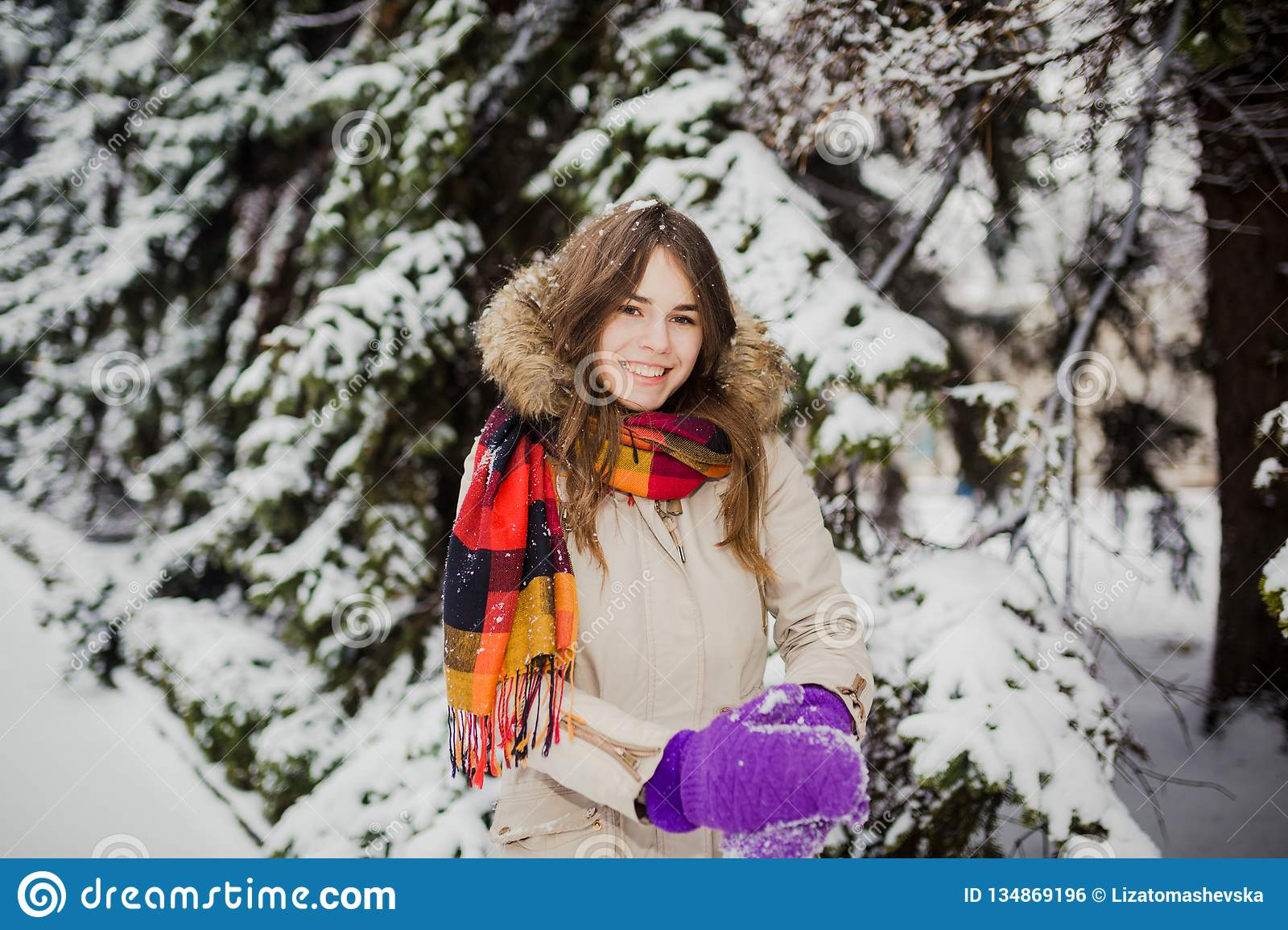 Beautiful young Caucasian people have the joy of happiness and fun in the winter in a snowy forest. Sculpt to make hands