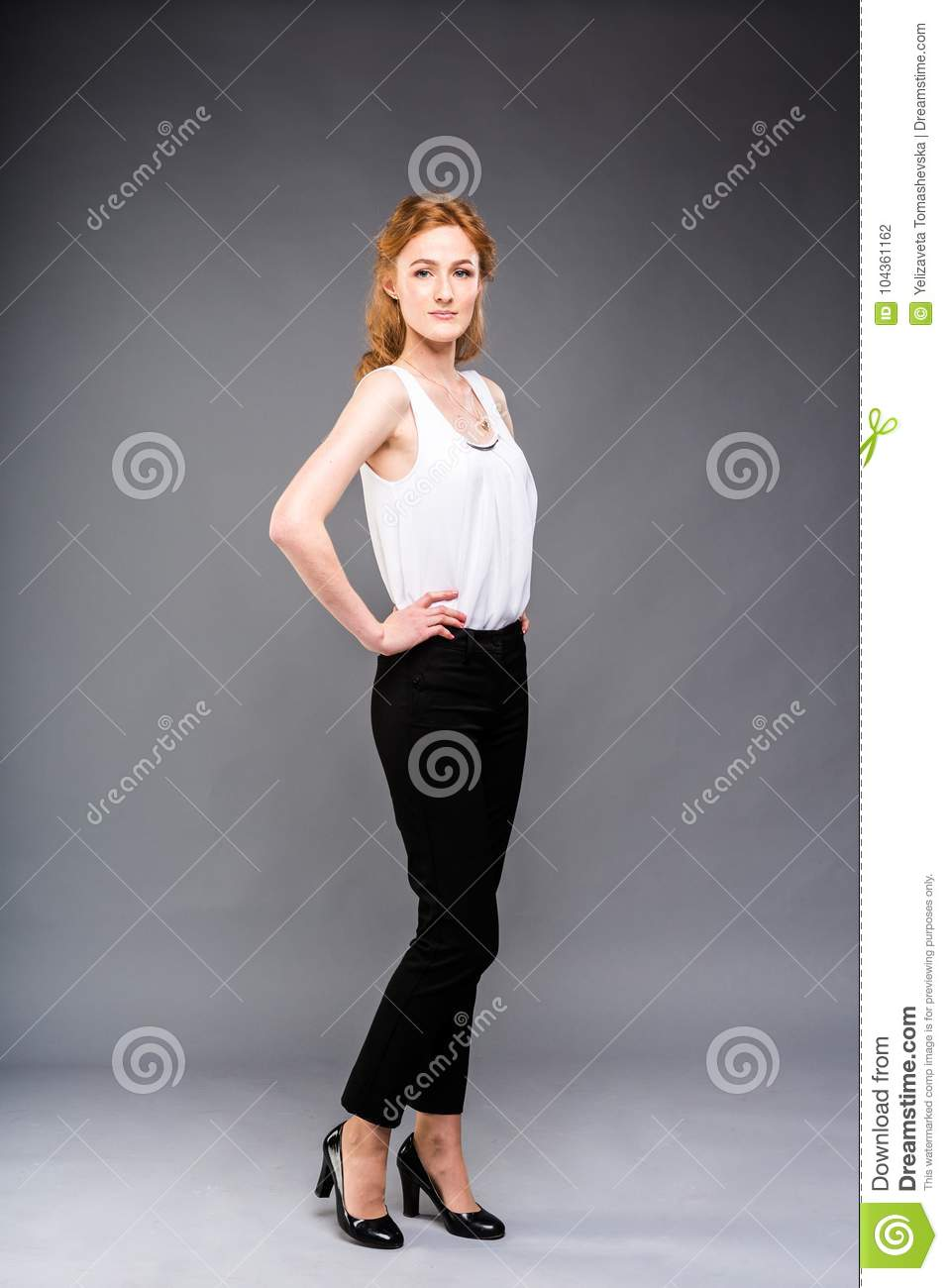 Beautiful young Caucasian woman with long red hair in high heels, black trousers and a white shirt stands in full growth on a gray