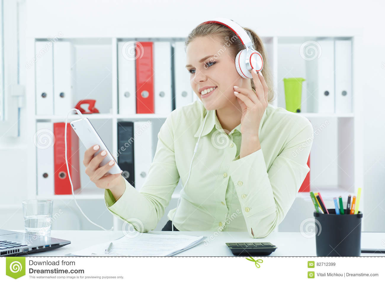 Beautiful young cheerful businesswoman listening music in headphones at office.