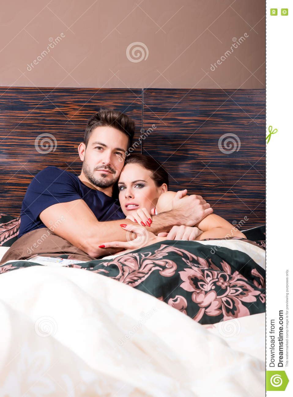 Beautiful young couple being scared in bed