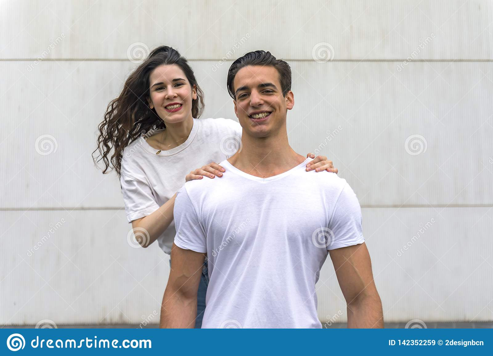 Front view of beautiful young couple hugging, looking at camera and smiling while standing outdoors