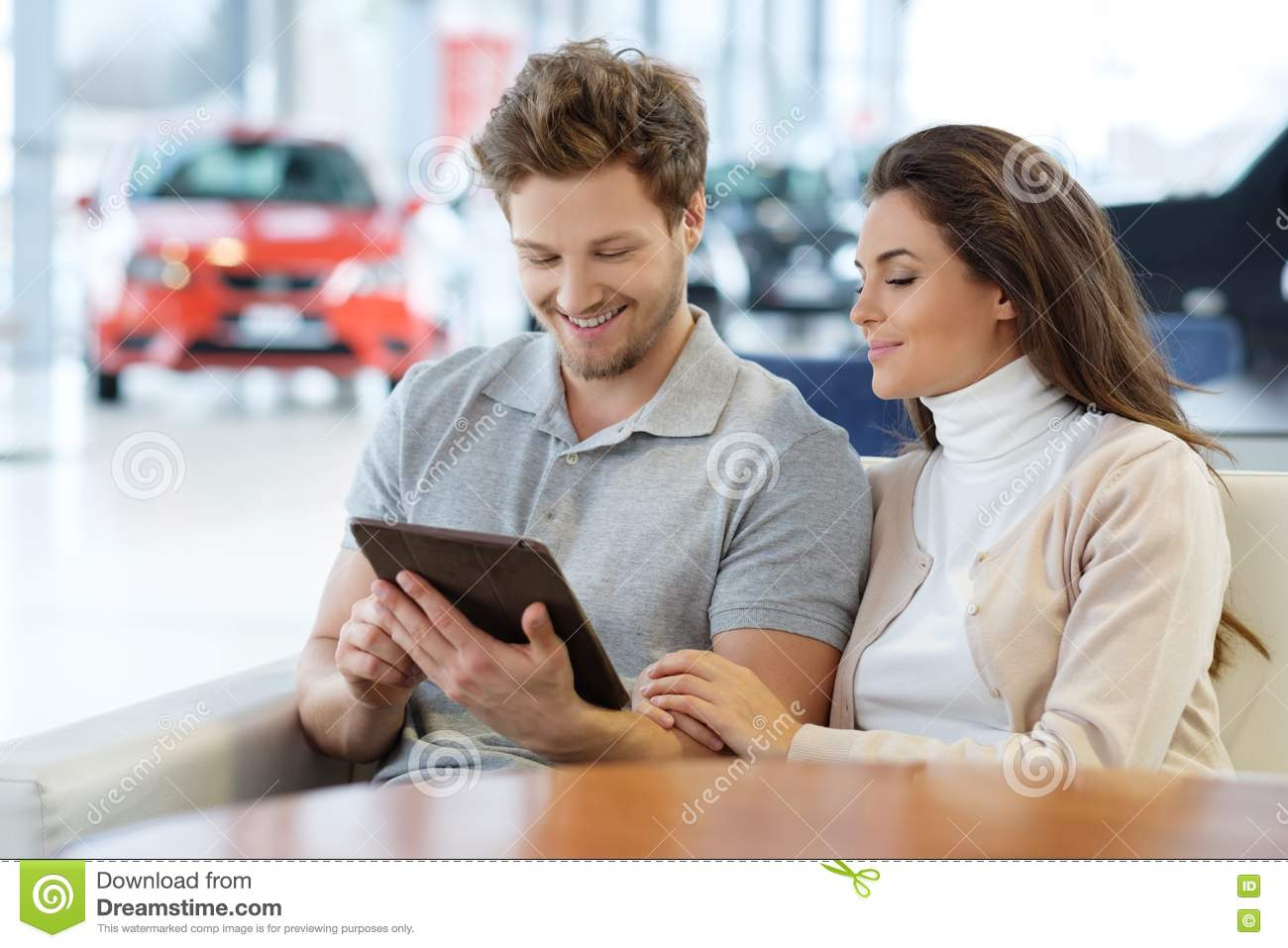 Beautiful young couple looking a new car at the dealership showroom.