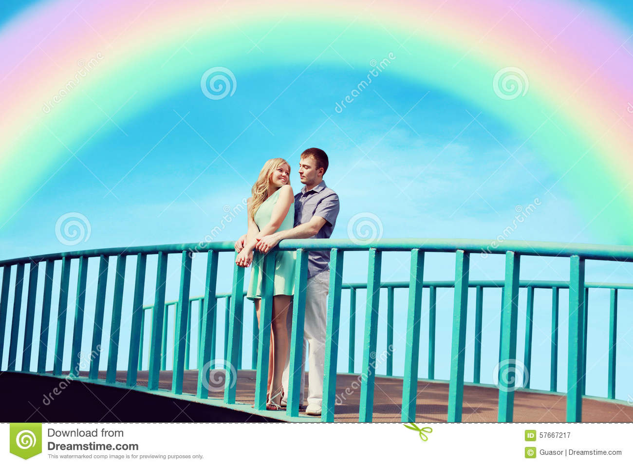 Beautiful young couple in love on the bridge over blue sky