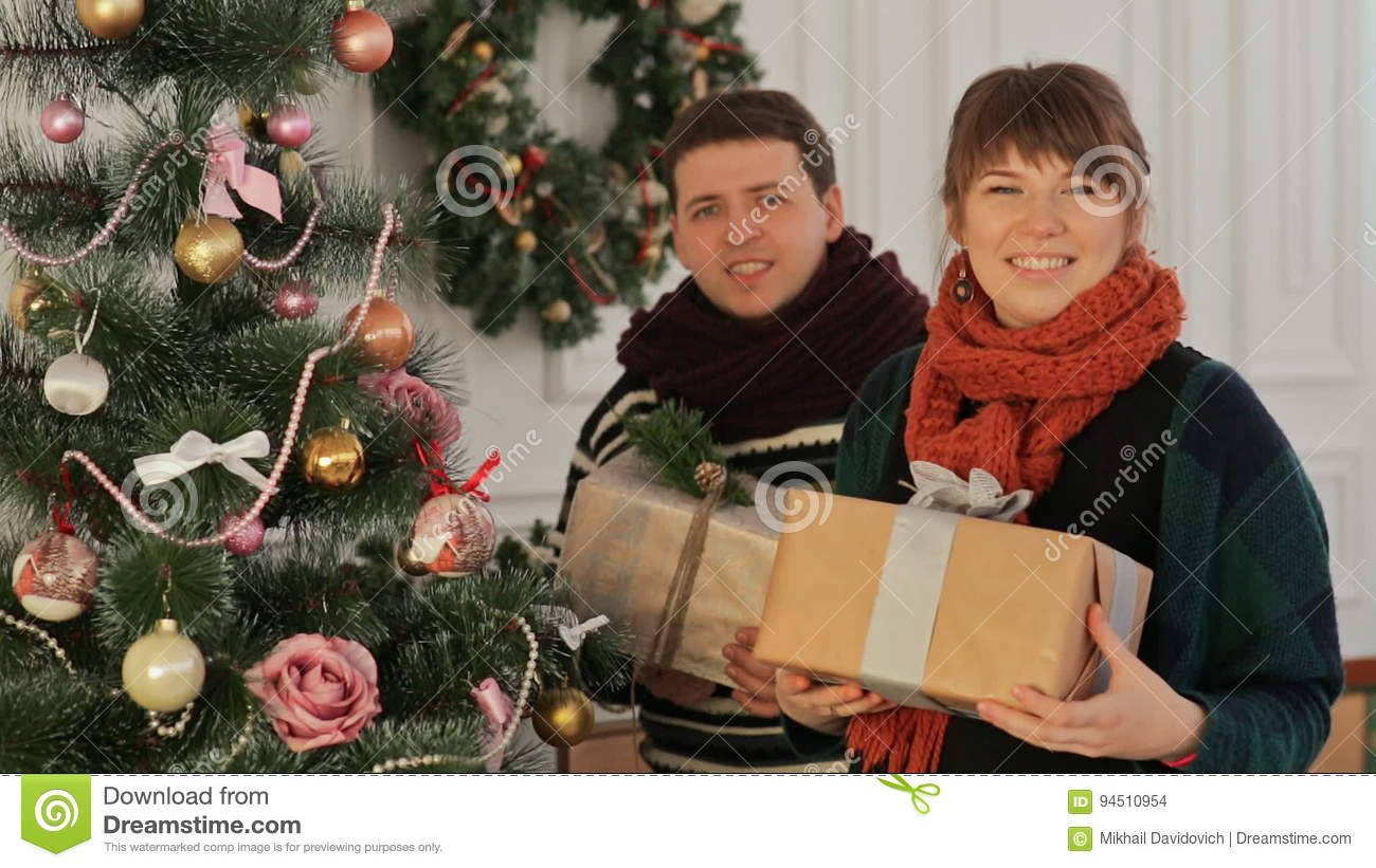 a beautiful young couple in love near the new year tree giving presents to the viewer christmas and new year themes stock footage video of excited