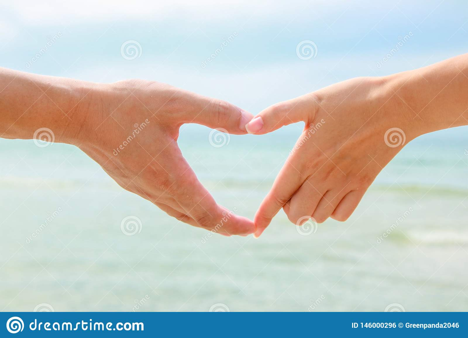 Beautiful young couple is making heart with the fingers