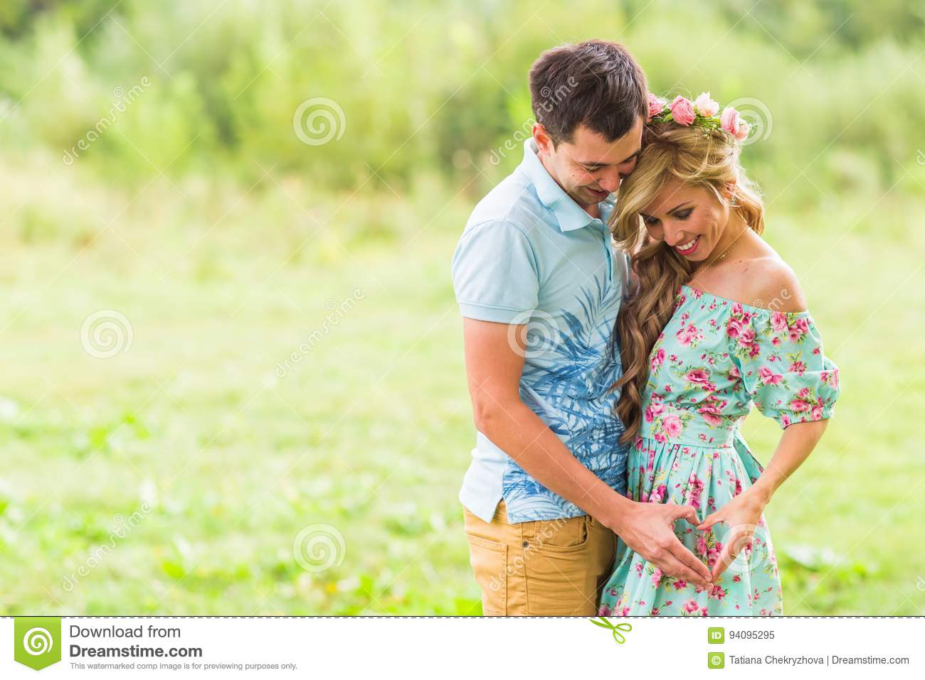 Beautiful young couple is making heart of fingers and smiling in nature