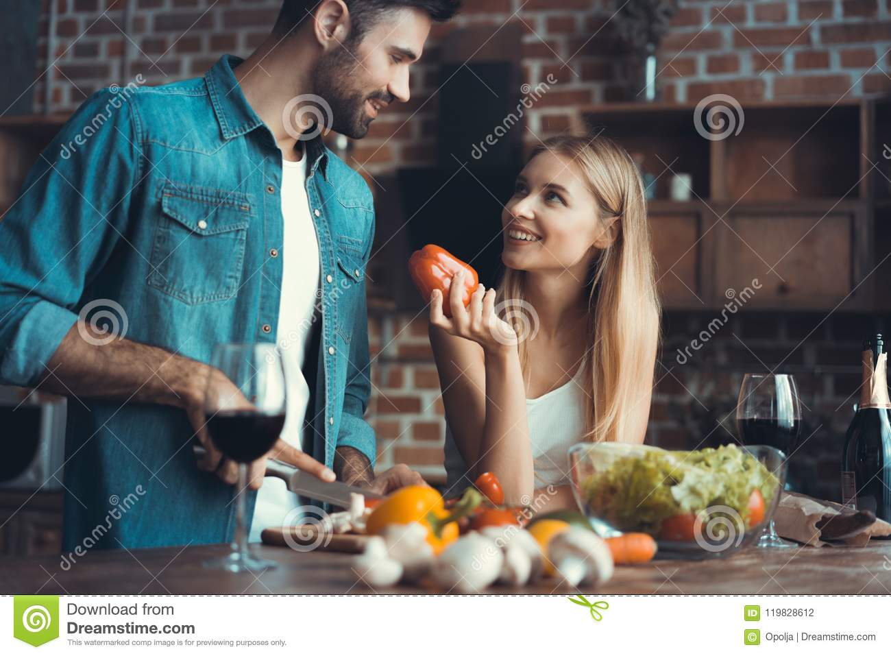 Beautiful young couple preparing a healthy meal together while spending free time at home.