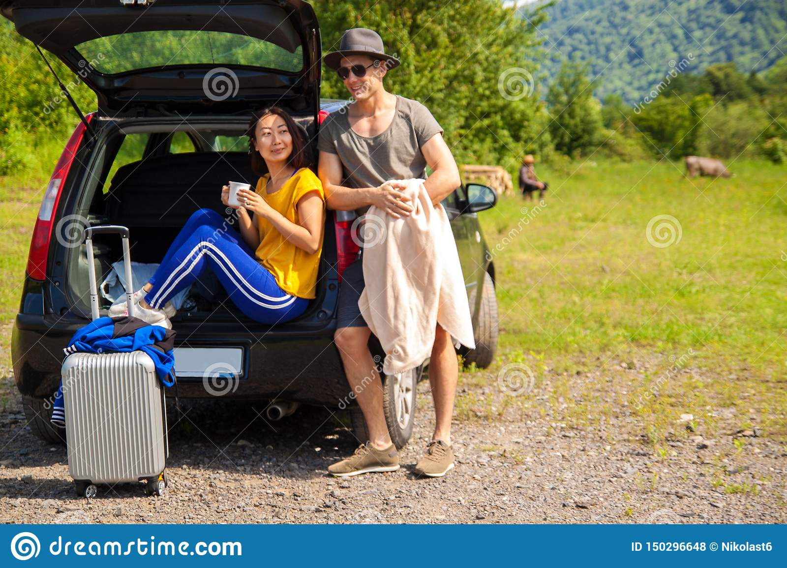 Beautiful young couple sitting in the trunk of a car and admire the beautiful scenery on the mountain.