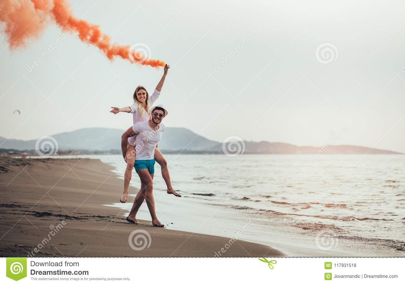 Beautiful young couple with smoke bomb in hand is standing outdoors