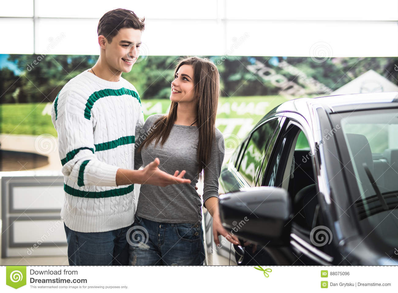 Beautiful young couple standing at the dealership choosing the car to buy. Man pointed on car.