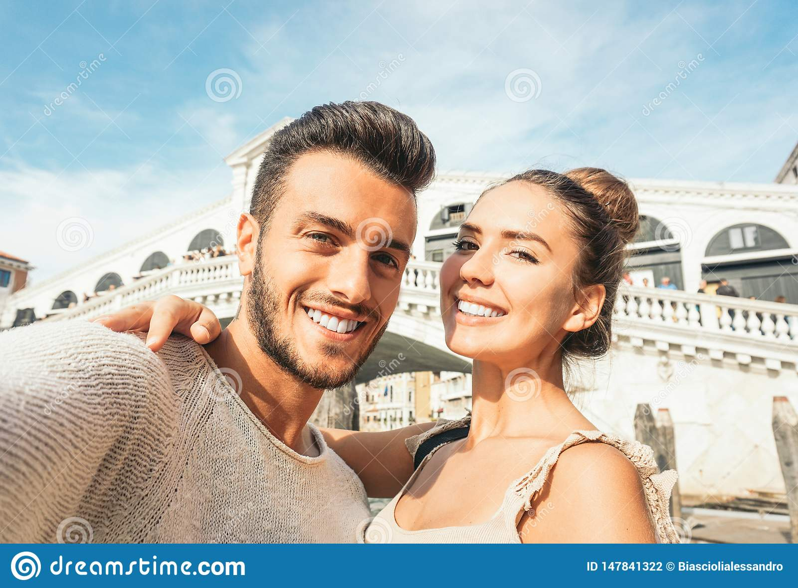 Beautiful young couple taking a selfie enjoying the time on their trip to Venice - Boyfriend and girlfriend taking a picture