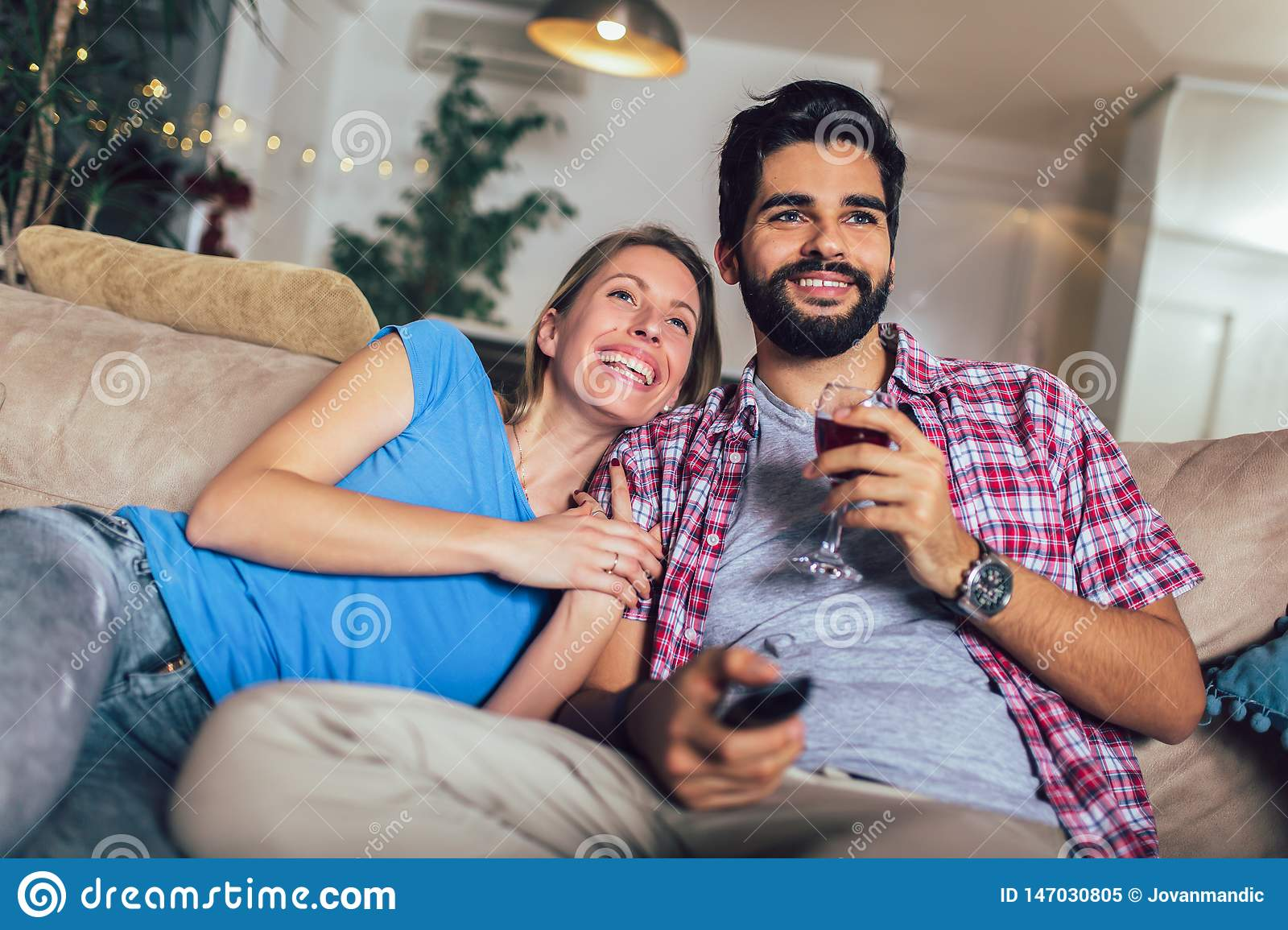 Young couple watching TV in living room