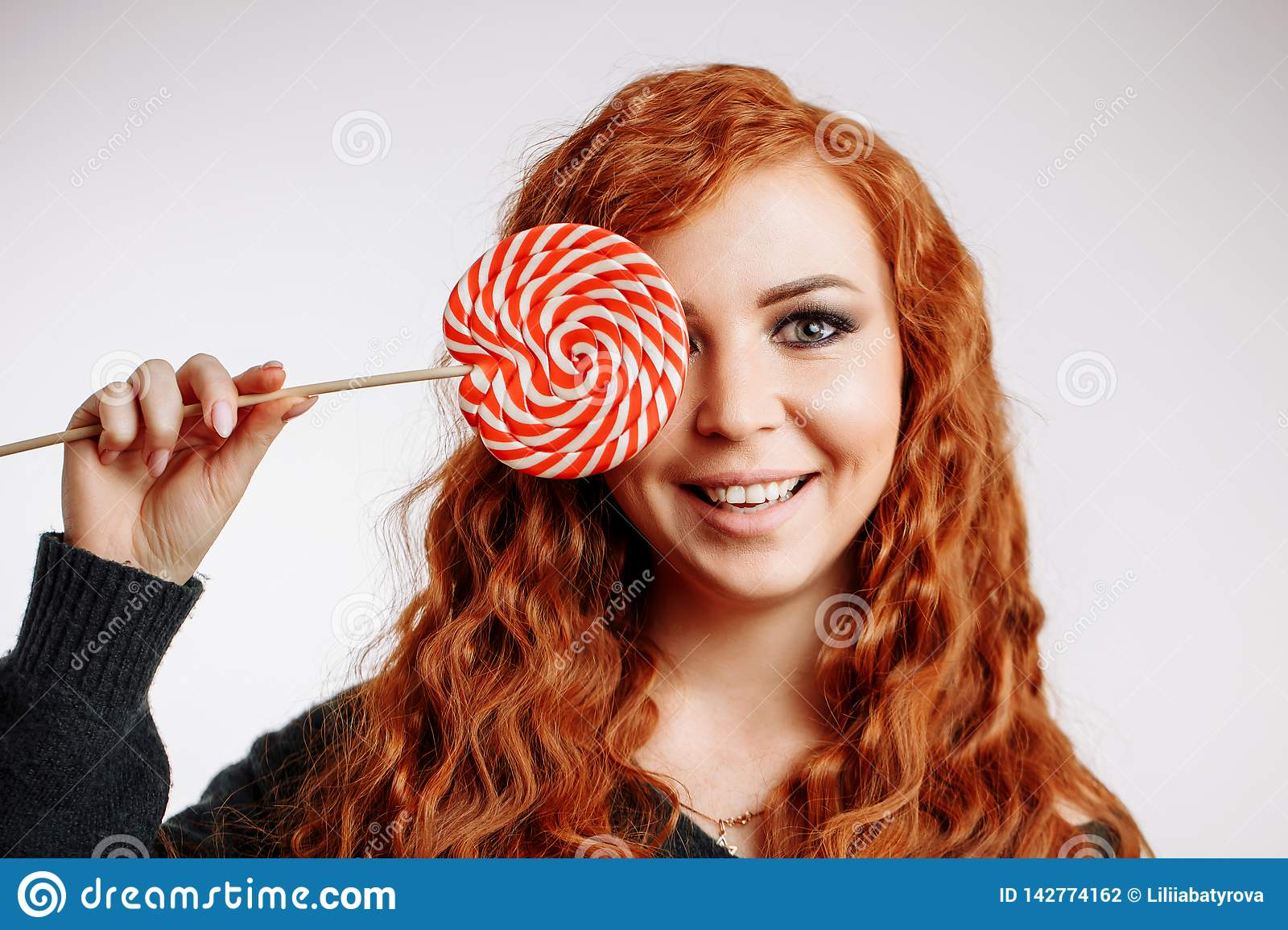 Beautiful young redhead woman holding a red white lollipop on white background