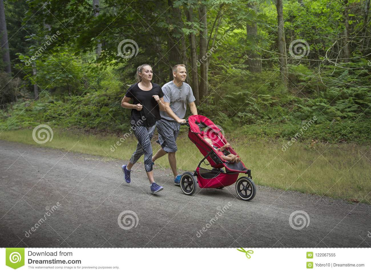 b9af3578889c Couple Exercising And Jogging Together Pushing Their Baby In A ...