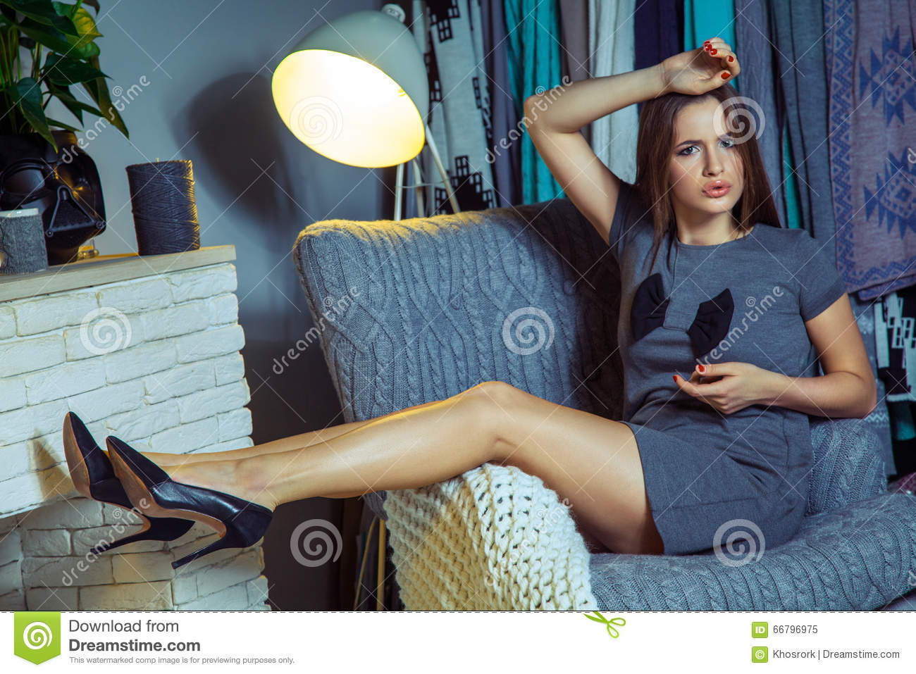 Beautiful young fashion caucasian model posing near armchair.