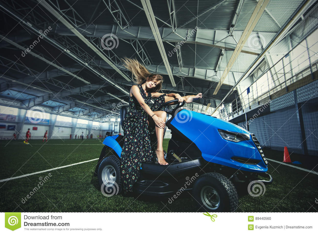 Beautiful young fashion model in a dress at a large sports stadium for the car care coating