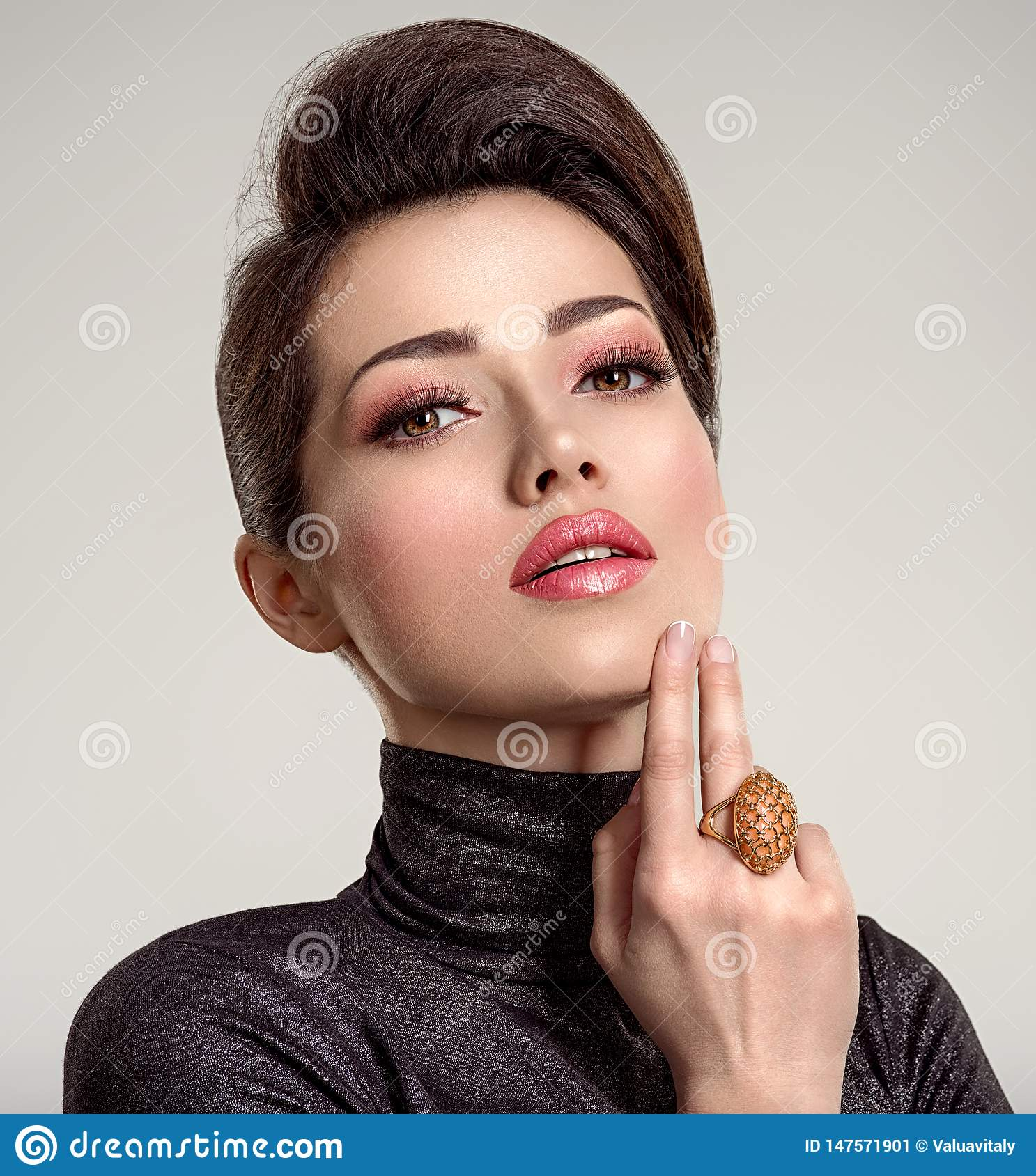 Beautiful young fashion woman with living coral lipstick. Attractive white girl wears luxury jewelry
