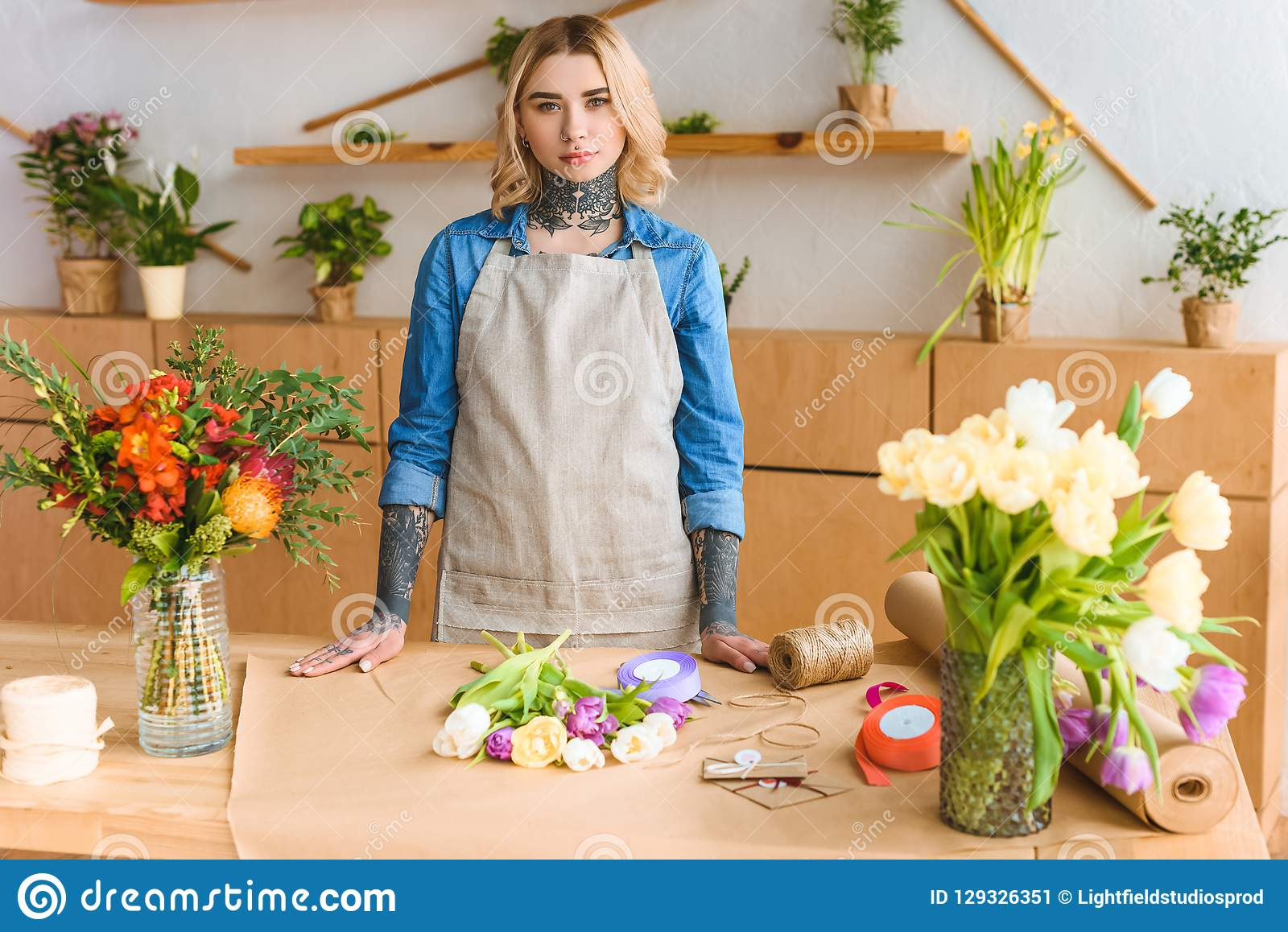 beautiful young female florist with tattoos looking at camera