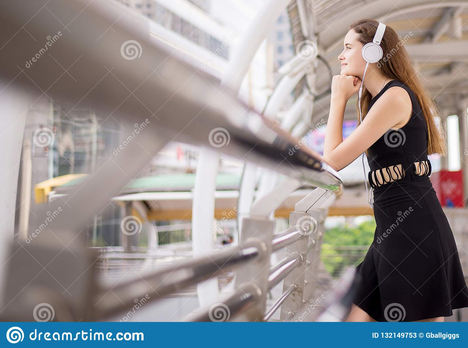 Beautiful young woman using headphones and listening to music in the city