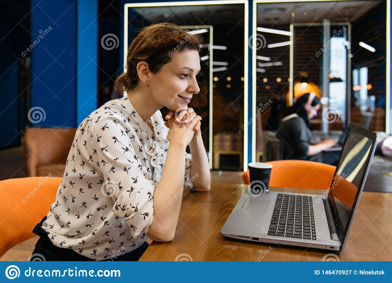 Beautiful Young Freelancer Woman Using Laptop Computer Sitting At Cafe Table. Happy Smiling Girl Working Online Or Studying And
