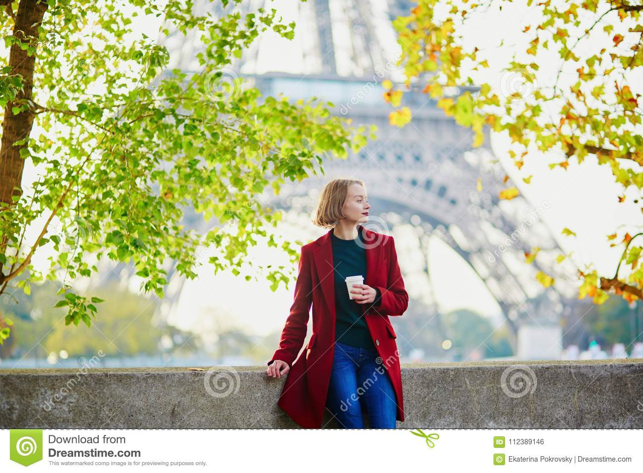 Beautiful young French woman near the Eiffel tower in Paris