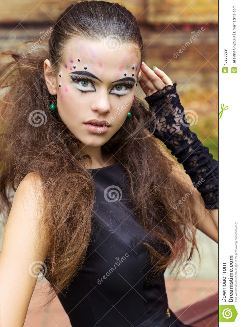 Beautiful young girl on the background of the leaves in autumn day on the street with fantasy makeup in a black dress