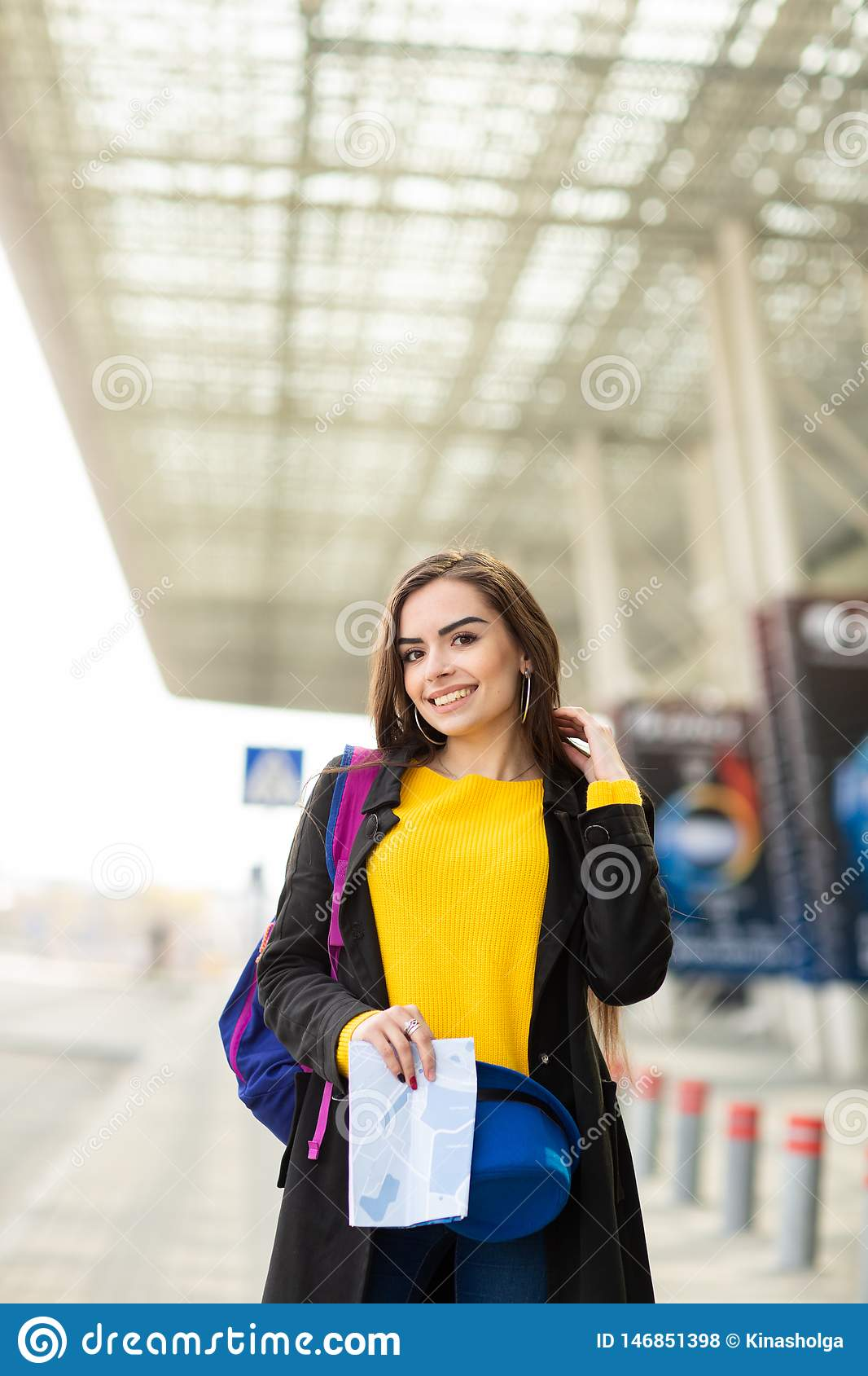 Beautiful young girl with a backpack behind her shoulder holding a map, in the street near the airport