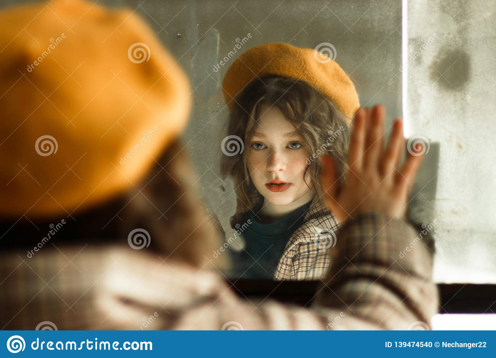 Beautiful young girl in beige hat looking at herself in the mirror
