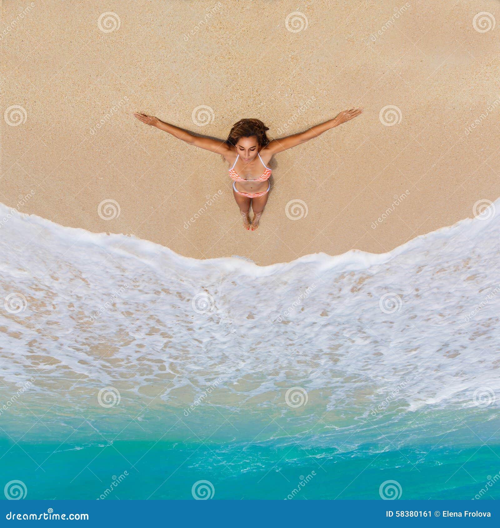 Beautiful young girl in bikini on a tropical beach. Blue sea in