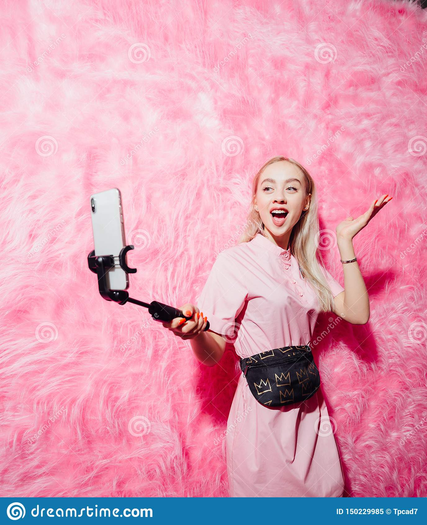Beautiful young girl blogger dressed in fashion pink dress make a selfie on the background of pink fur wall in the show