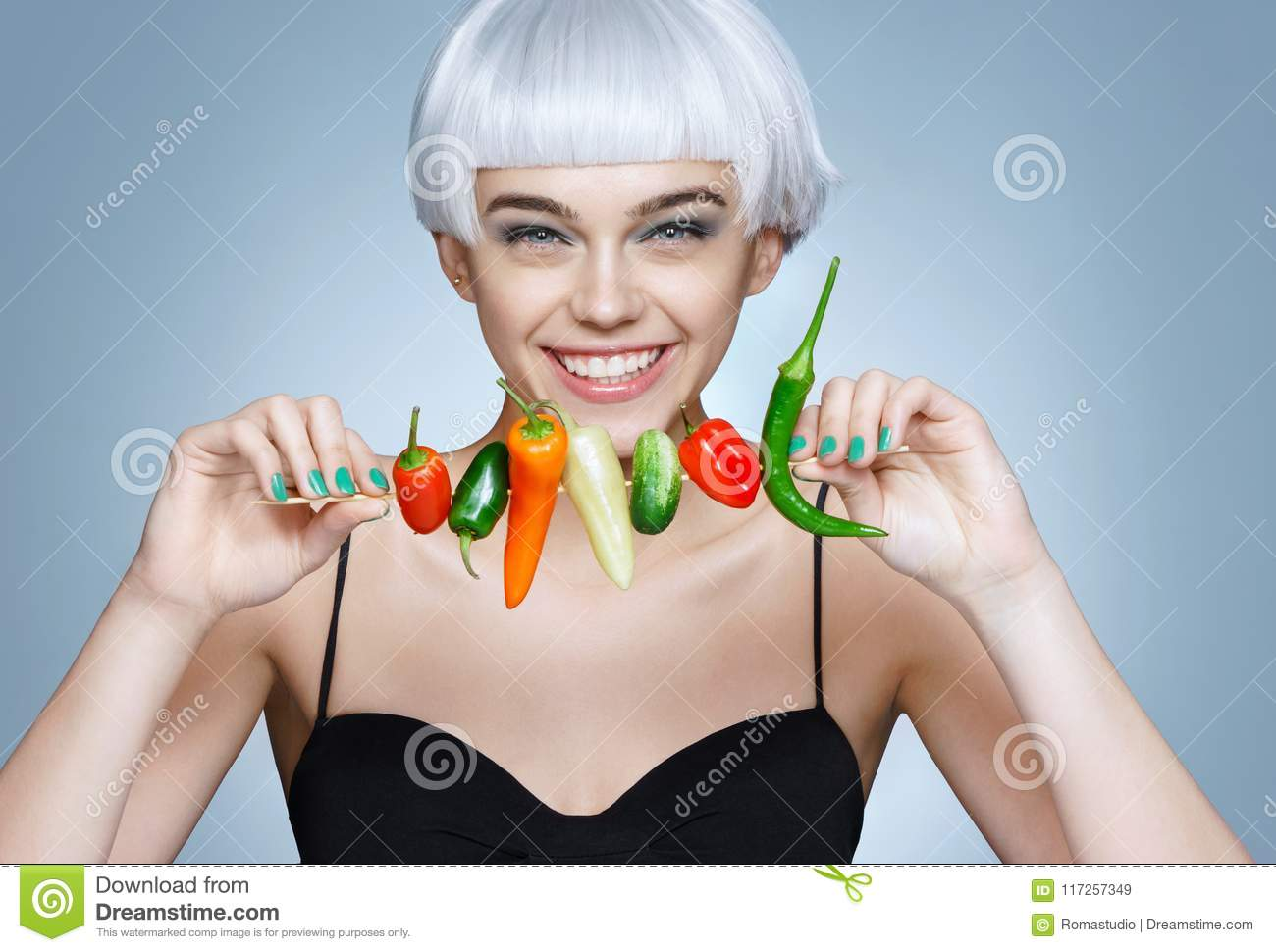 Beautiful young girl with different peppers.