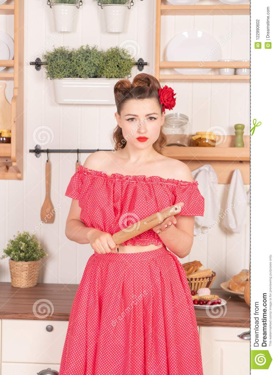 Beautiful young girl with flower in her hair posing in red pin up polka dot dress at home in the kitchen