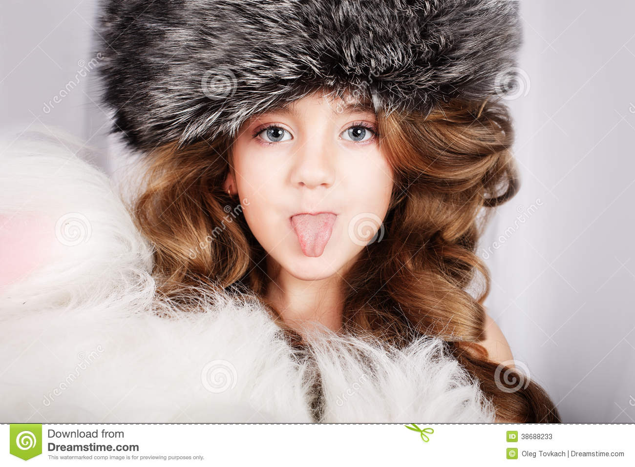 Beautiful Young Girl In Fur Cap Puts Out The Tongue Stock