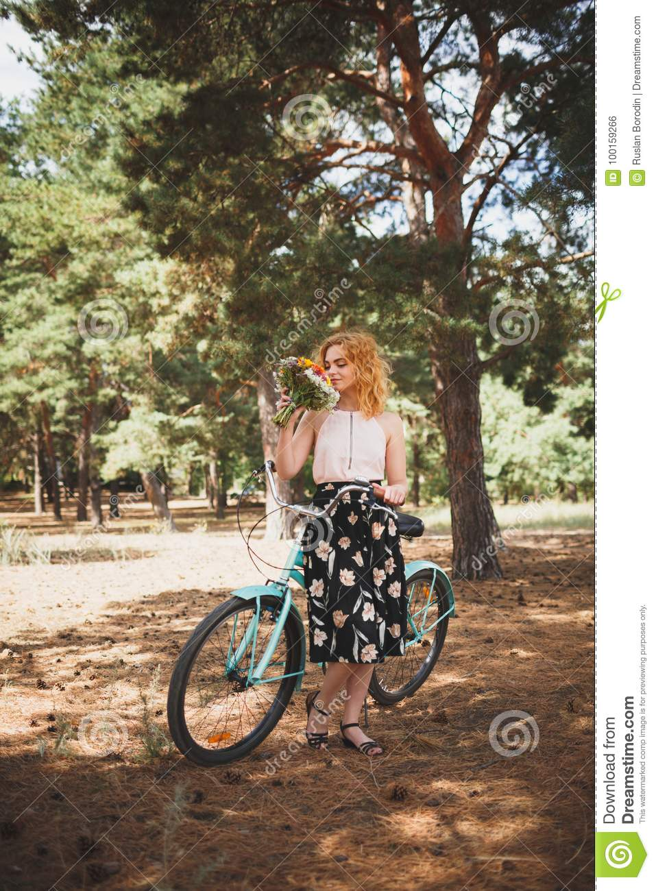 Beautiful young girl with her bike cruiser and flowers on autumn field. The best time to walk with a bicycle.