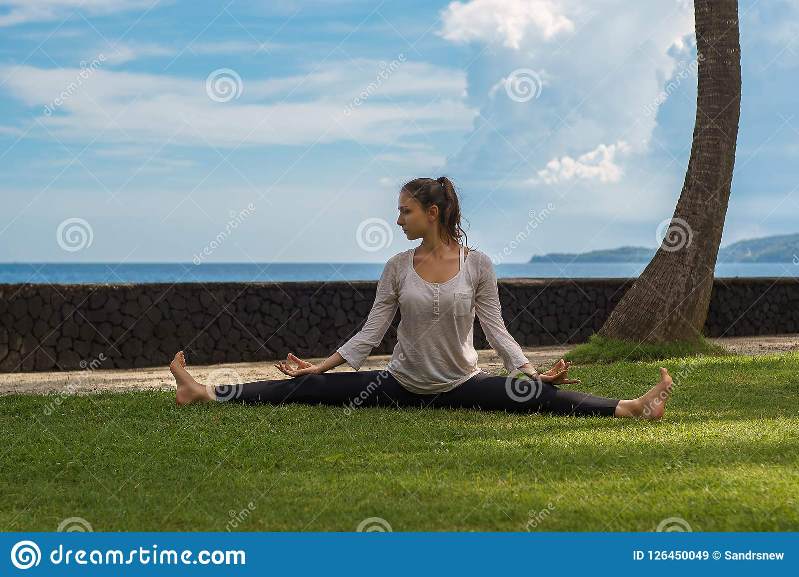 Beautiful young girl in leggings and tunic makes yoga practice, meditation on the ocean beach in Bali Indonesia