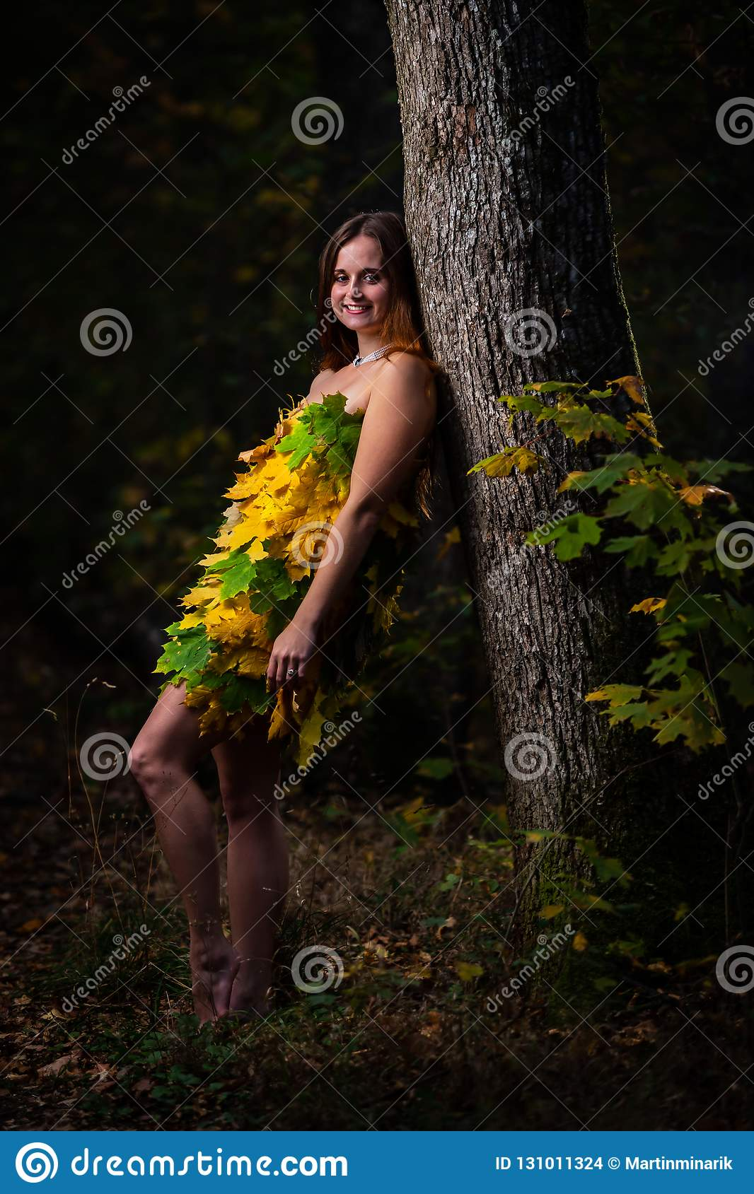 Beautiful young girl with long hair leaning to the tree, wearing dress made from colorful leaves in the autumn forest
