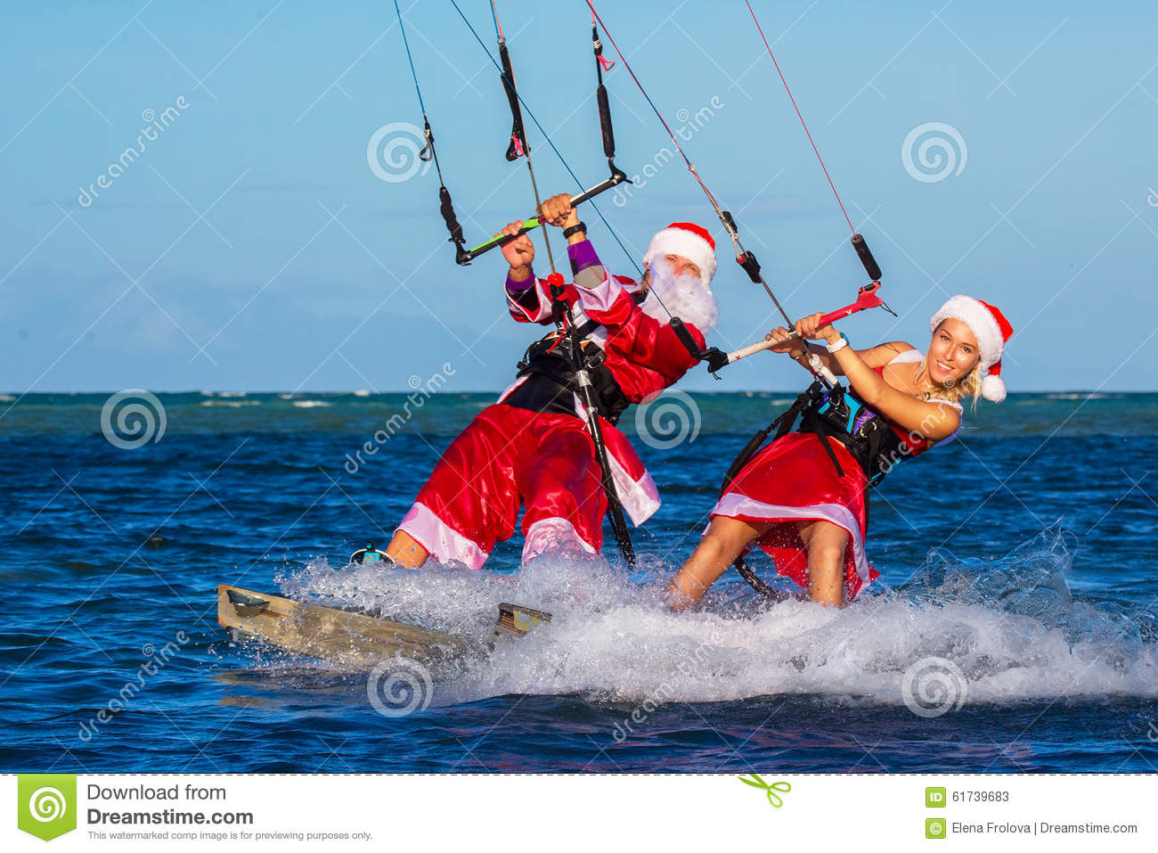 Beautiful young girl and man on the kites in the costume of Santa Claus. Christmas and New year on a tropical island. Extreme