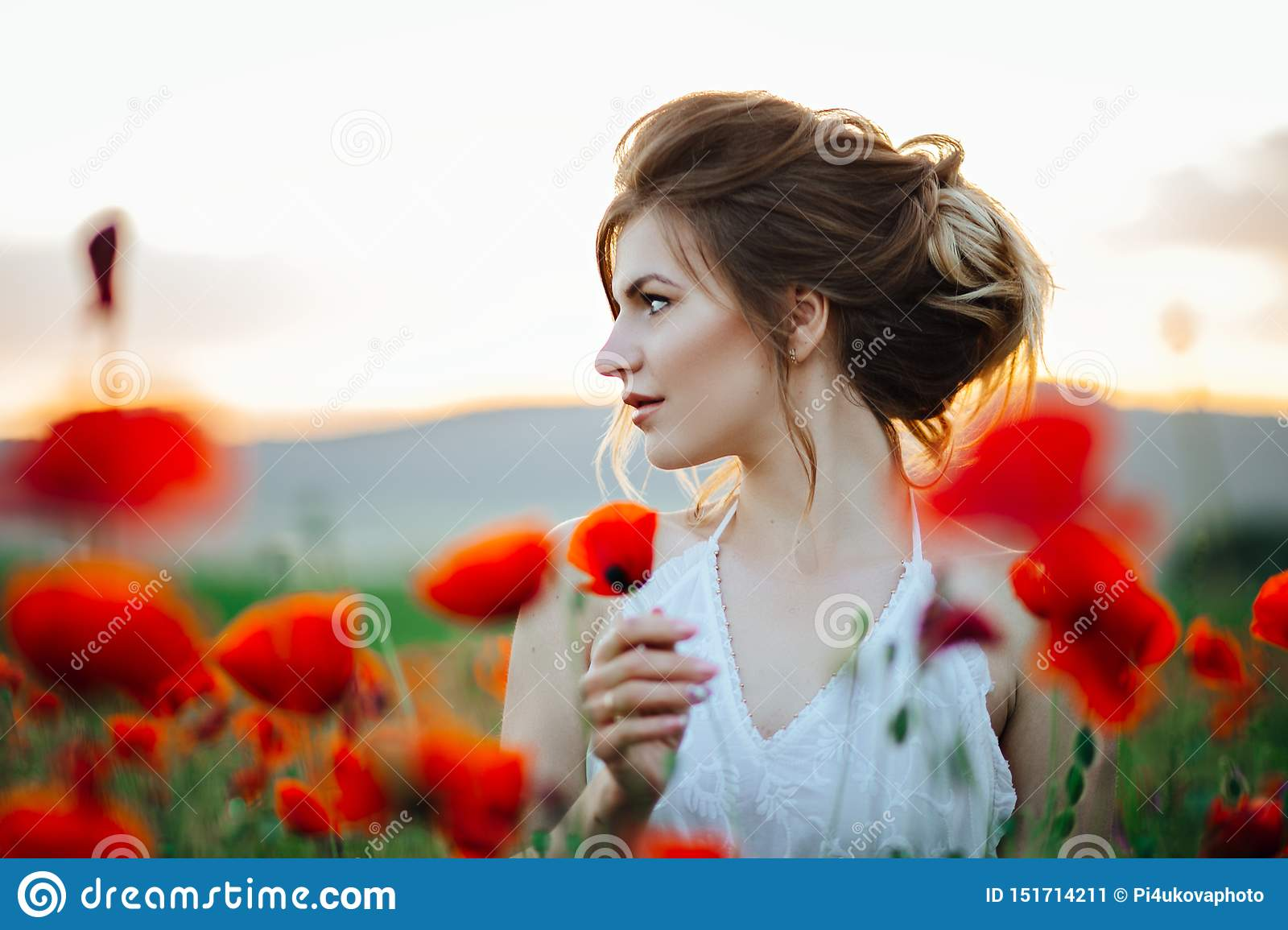 Beautiful young girl in poppy fields at sunset. Beautiful nature.